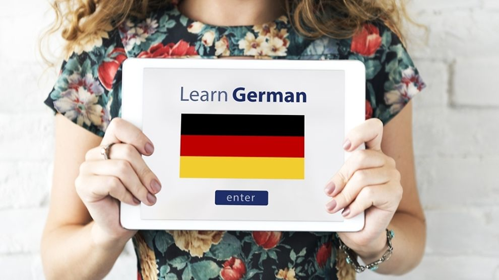Women holding a tablet, which shows the words leran german and the german flag