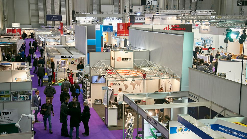 Representatives of technical branches wandering throught the aisles of the Hamburg Messehallen Trade Fair.
