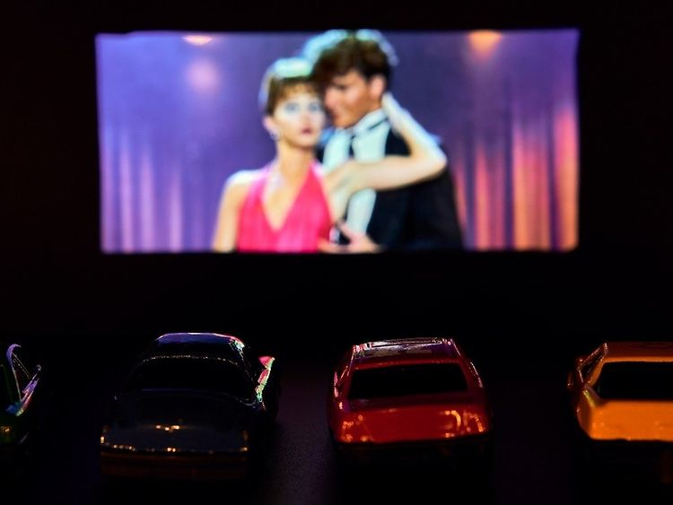 Cars parked in front of a outdoor movie screen