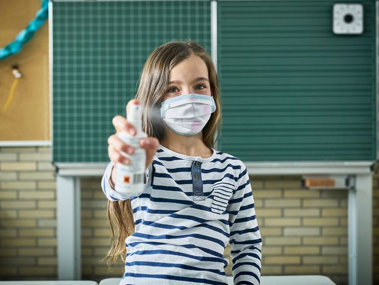 Girl in classroom wearing face mask and holding hand sanitiser