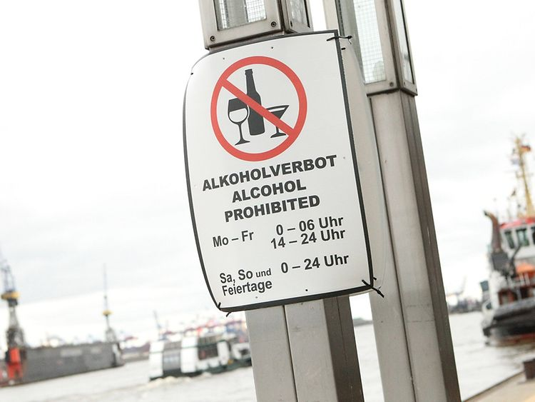A sign hangs on a pole at Hamburg harbour, indicating that alcohol is prohibited in this area at certain times
